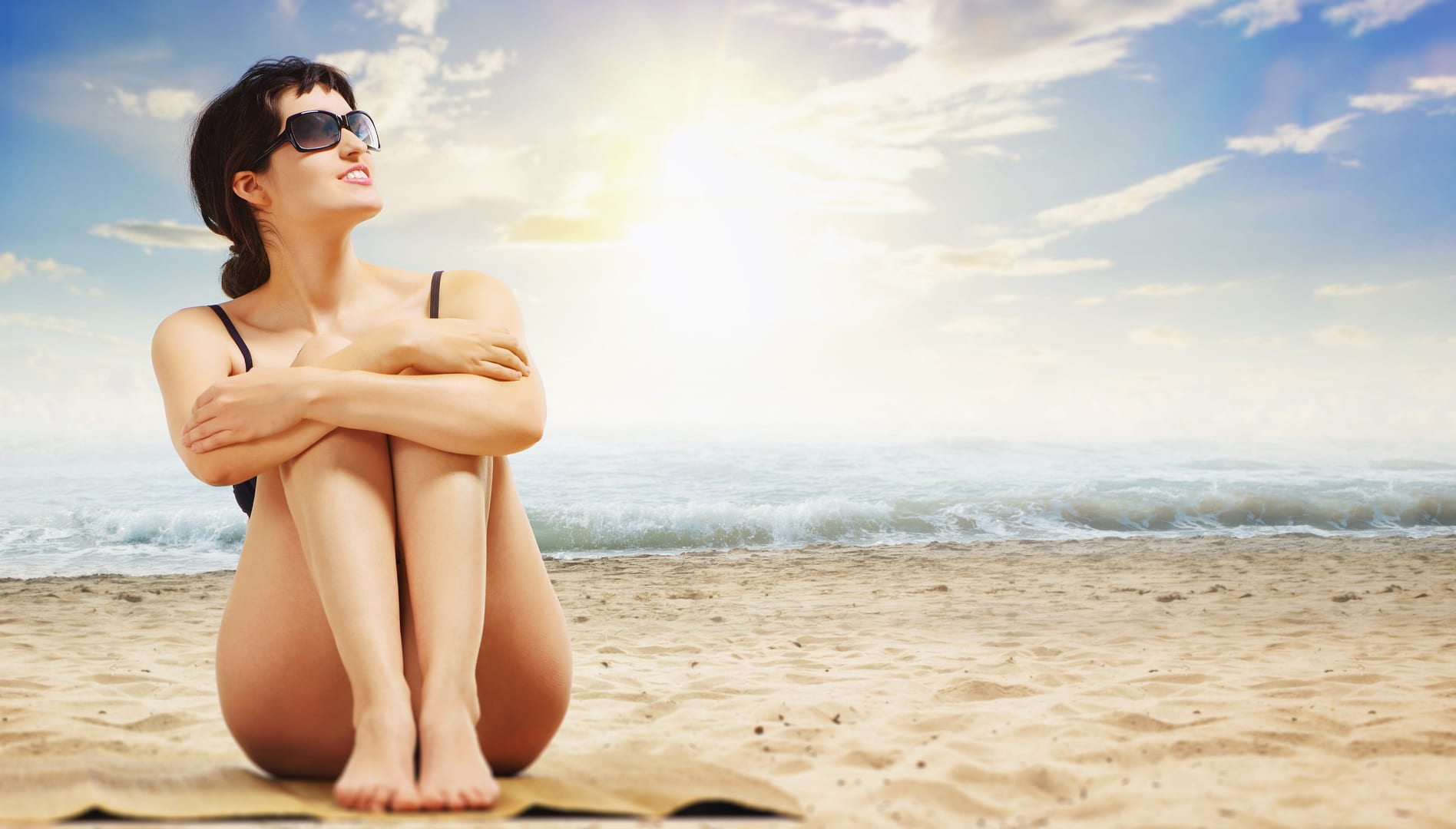 Woman enjoying a day at the beach. Mosaic Spa can help protect your summer skin.